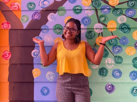 Belize: a young woman, Renata, stands in front of a colourful wall and raises her hands in a playful pose with a smile.