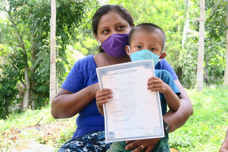Belize: a mother holds her child who shows his birth certificate. Both are wearing a face mask for COVID-19 prevention.