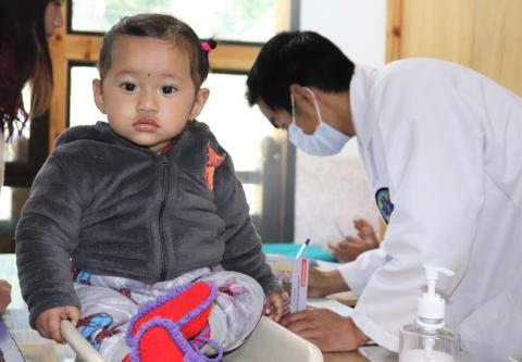 A toddler gets weighed at the Mother and Child Hospital in Thimphu