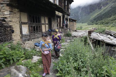 Two young mothers taking their babies to the village health worker for growth monitoring