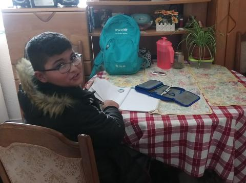 Bilal writing homework in his home