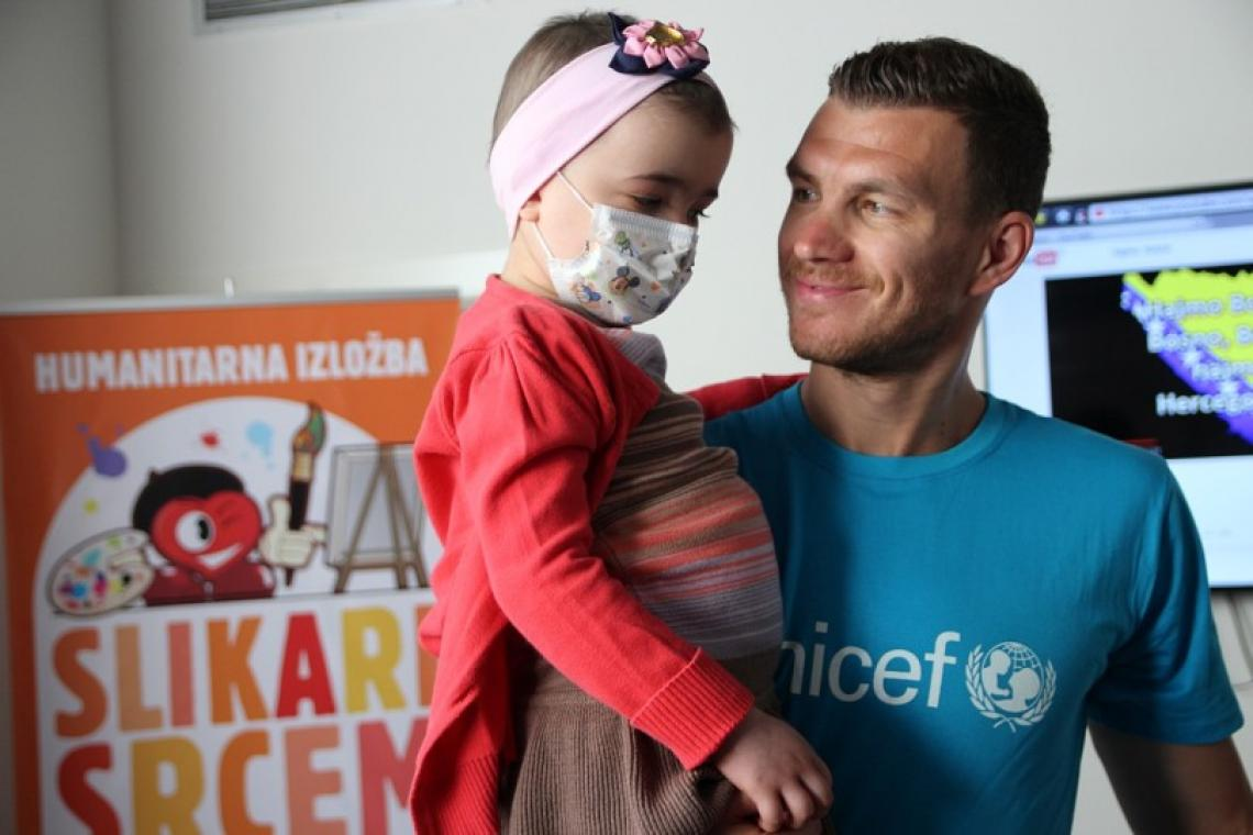 Edin Dzeko, UNICEF Bosnia and Herzegovina Ambassador with a child