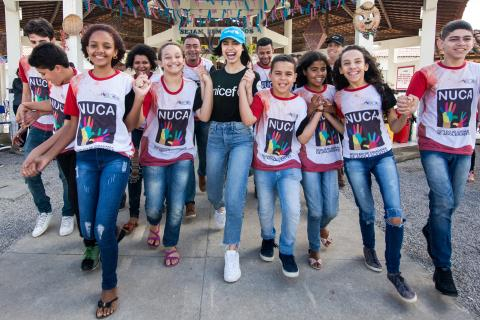a atriz norte-americana Sofia Carson caminha em direção à câmera com outros adolescentes. Ela veste camiseta com o logo do UNICEF e os adolescentes vestem camiseta com a estampa do NUCA