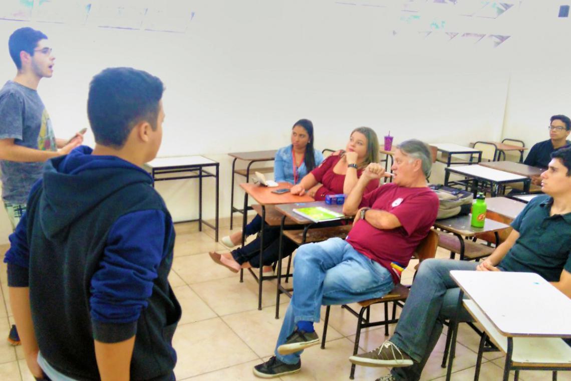Dois estudantes estão em pé falando para um grupo de quatro pessoas que estão sentadas em carteiras escolares