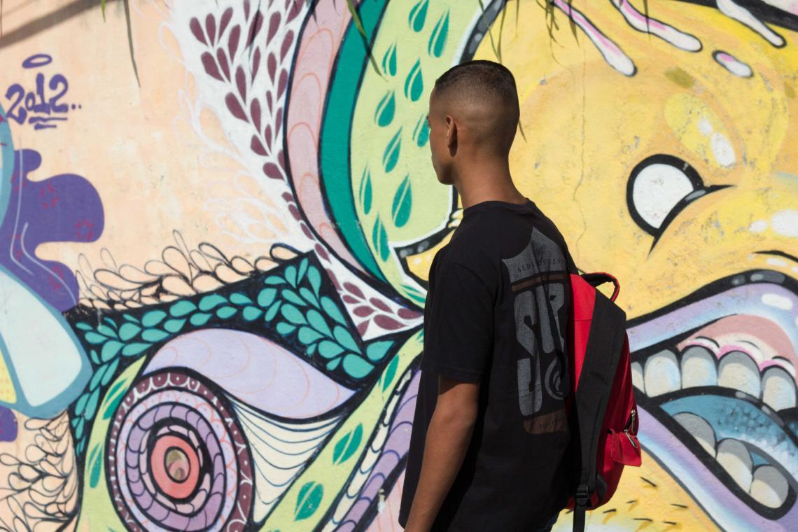 Adolescente de costas, carregando uma mochila, passa em frente a um grafite de rua