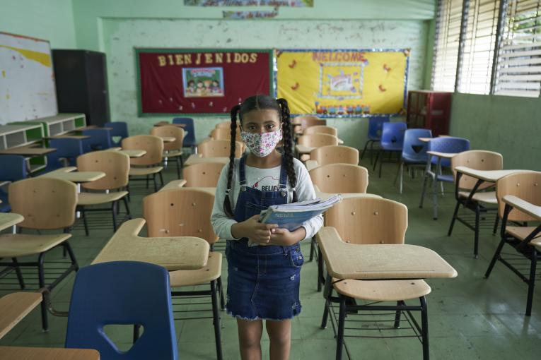 uma menina usando máscara e segurando material escolar está parada em pé no meio de uma sala de aula vazia