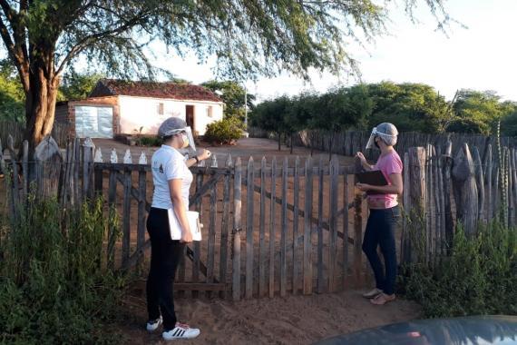 duas mulheres estão na cerca de entrada de uma propriedade rural