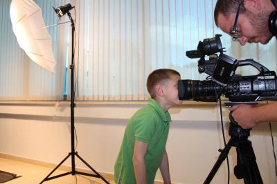 A boy has hidden his face into a camera. A camera man is sitting behind the camera and is recording