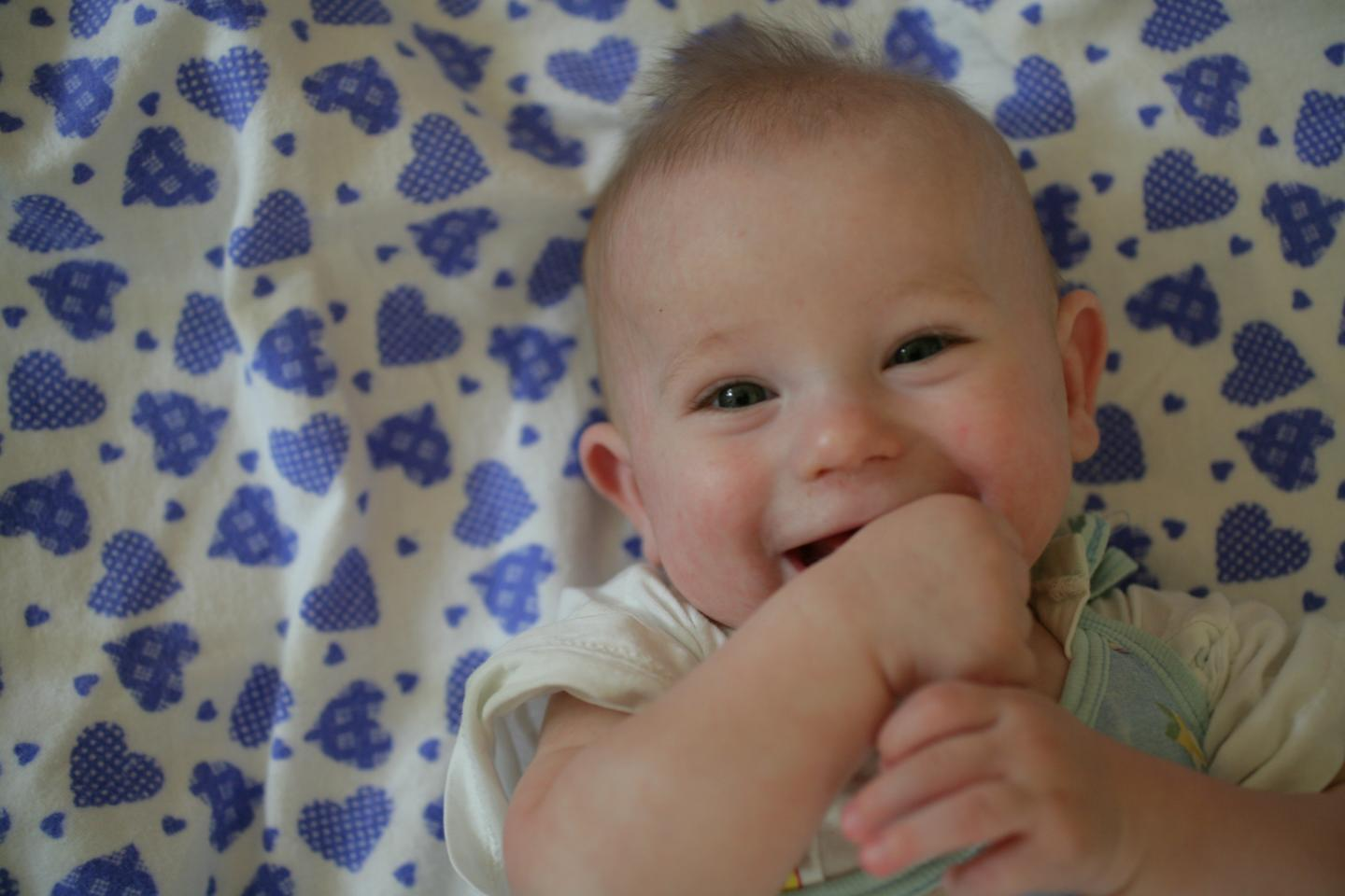 a few months old baby is smiling with hands in his or her mouth