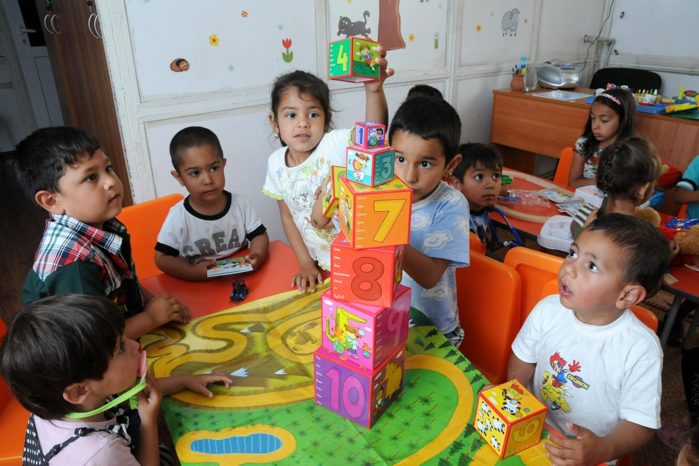 Children learning and playing at the kindergarten. They are building a tower of cubes