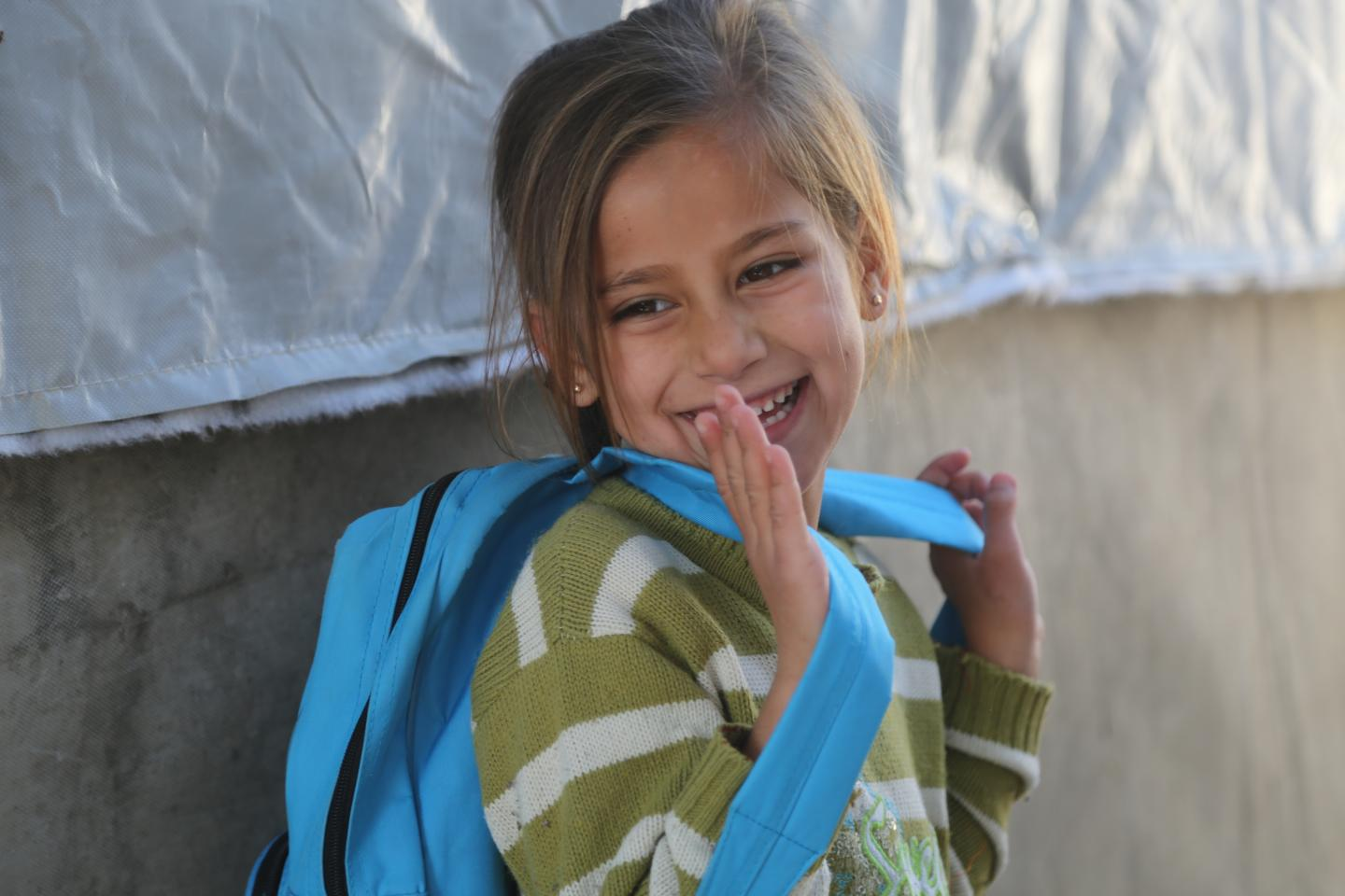 A refugee girl is smiling with her new school backpack, provided by UNICEF