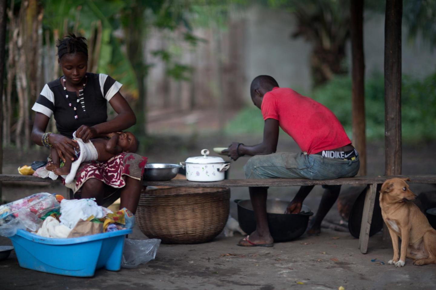 Amina Kamara, 15, tends to her son, Ali, 6 months, while her husband, Lamine, serves food from a cooking pot in Motonko Village, Ribbi Chiefdom, Moyamba District