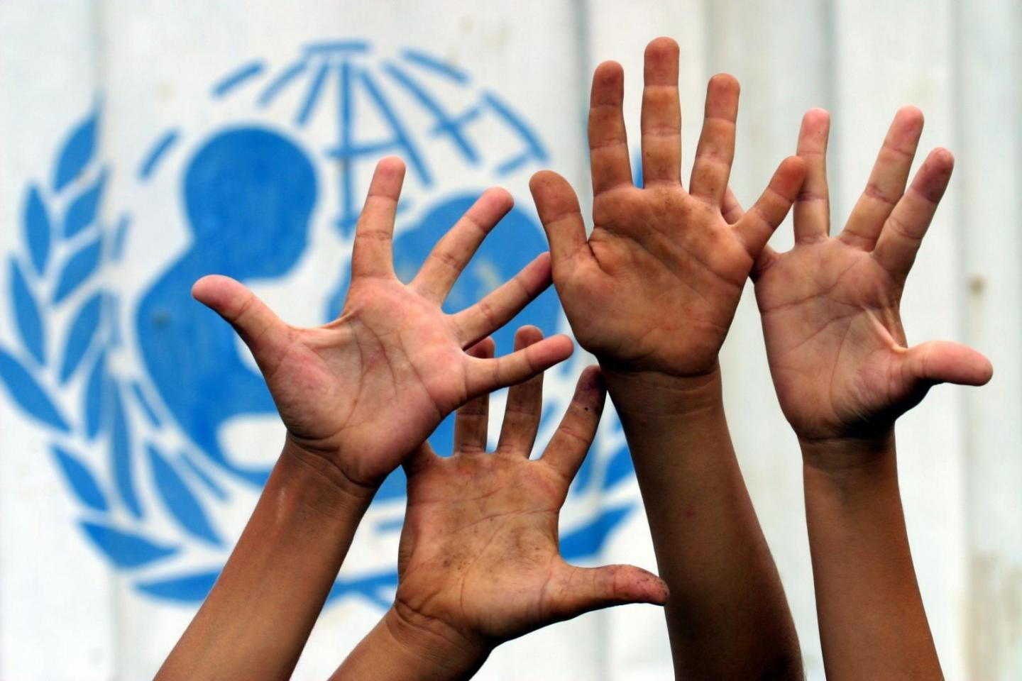 Hands raised in the air in front of UNICEF's logo