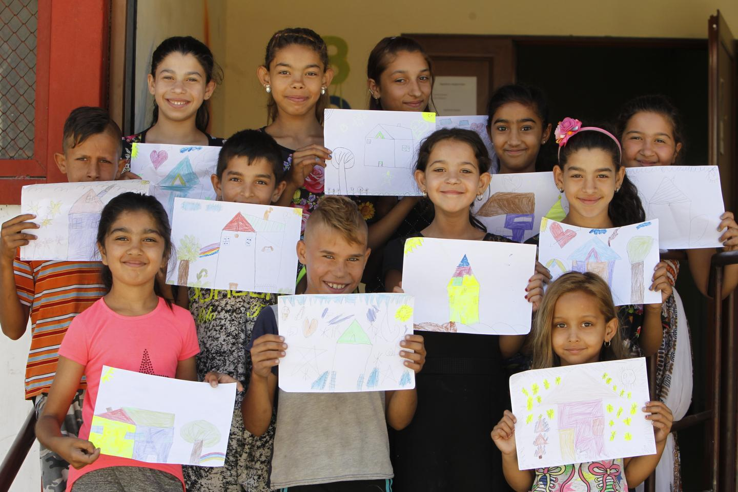 Children posing for picture holding drawings