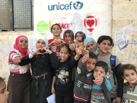 Refugee and migrant children are smiling and pose for photo in front of the refugee center