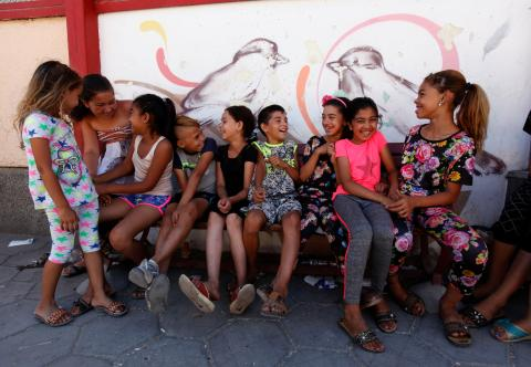 Children from vulnerable communities are sitting on a bench and having fun, behind them there are beautiful graffiti