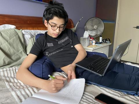 A teenager is learning at home