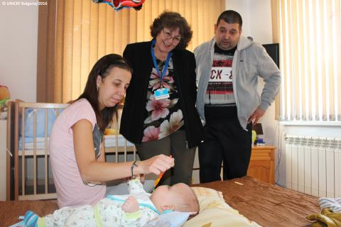 A visiting nurse is helping a family and their baby
