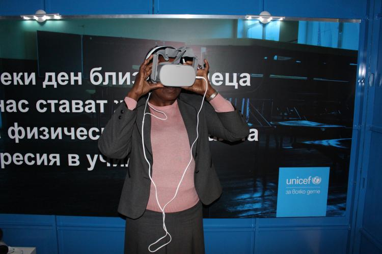 Dr. Jane Muita wearing virtual reality glasses at the opening of an interactive instalation
