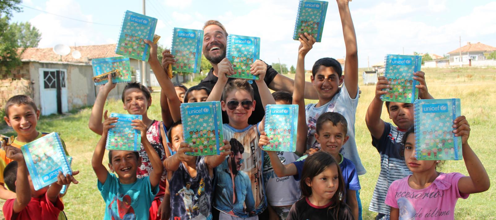 Boys and girls pose with unicef notebooks on the green field.