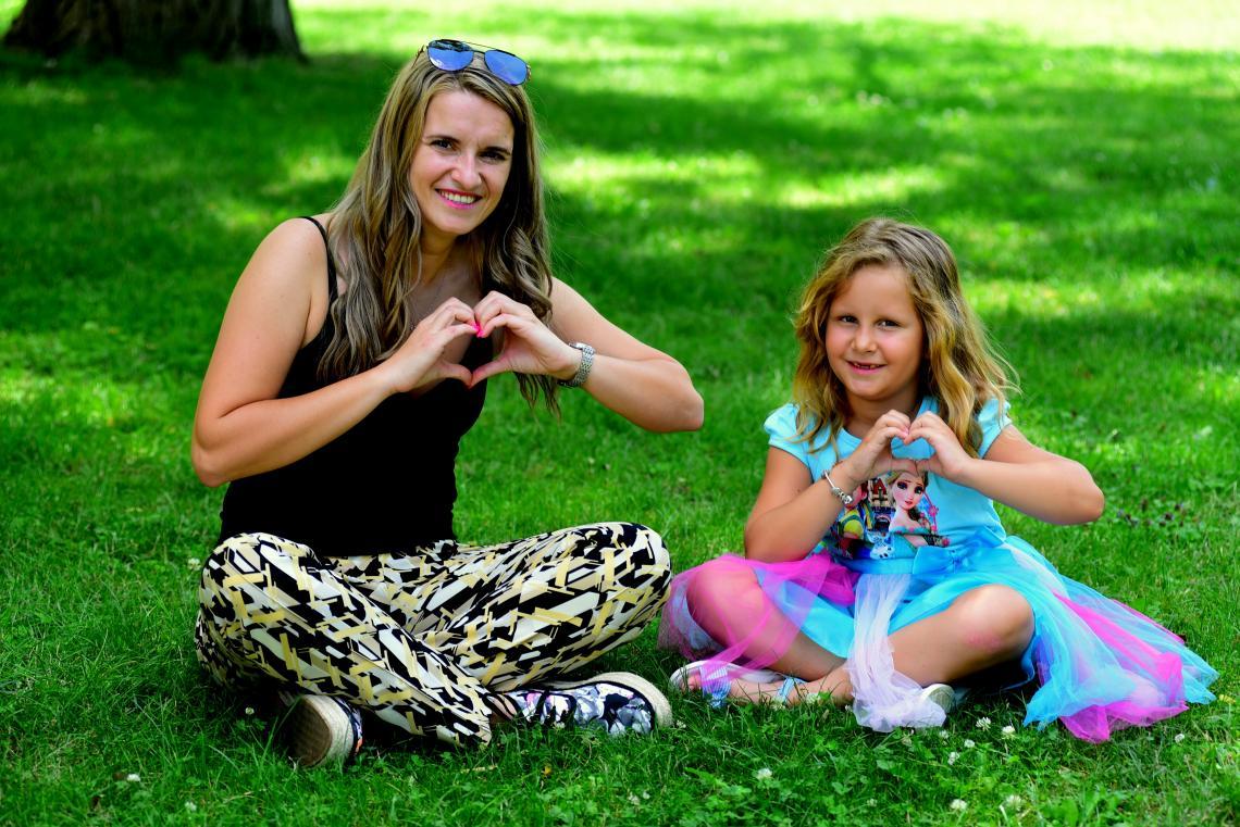 Силвия и Ема - майка и дъщеря се усмихват в парка, докато общуват и изпращат сърчица с ръце