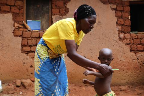 Bibiane Basabakwishi, 56, measures the arm of a child to check signs of malnutrition in Tangara, Ngozi province