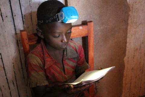 Nadia Kampimbare is looking at her school lessons wearing the solar lamp