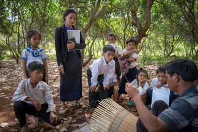 Chea Lach takes her class for an outdoor activity in the local village to learn about the animals in the area and the local tradition of basket weaving.