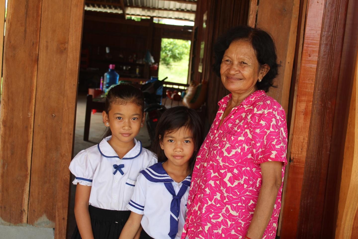 Two primary school students at O Kandea School with their grandmother in Sambo District, Kratie. August 2019.