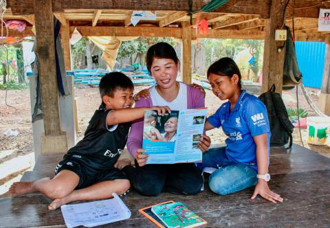 Mankak (Left), Van Veuy (middle) and Van Niza (right) read a printed leaflet on MHPSS at their home