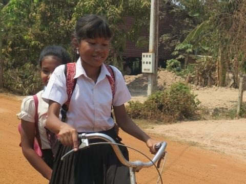 A child undergoing reintegration from an orphanage cycles home from school