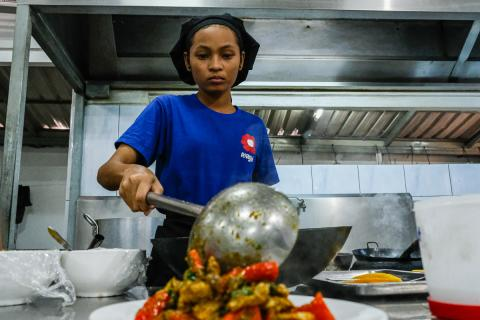 Chanthou 16 years old, a trainee at Sandan Restaurant in Sihanouk vile is finishing her cooking for customer.
