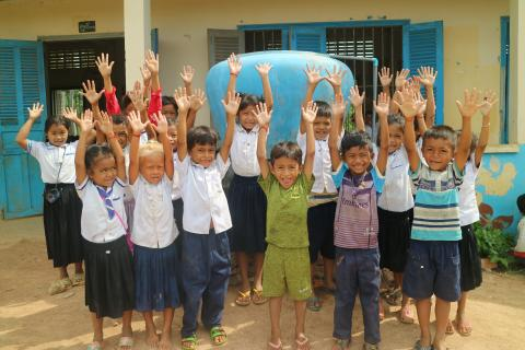 Students at Ork Yom proudly show their clean hands after the group hand washing activity.