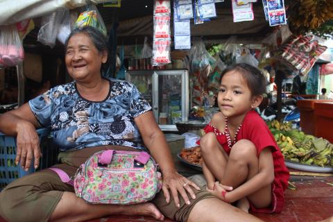 67-year-old Svay Rouen (left), with her eight-year-old granddaughter, in a community in Phnom Penh. Rouen cares for her three granddaughters after their parents divorced