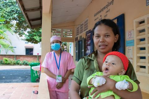 A woman holds her infant son at health centre