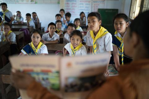 A female teacher reads a book with her class at Kampong Thmar Primary School