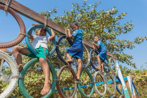 Three boys play a climbing game at Prek Kov Primary School