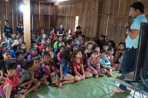 Children gather in a small wooden home,  built on stilts, to view an episode of Prai Krala,  a TV series produced by UNICEF.