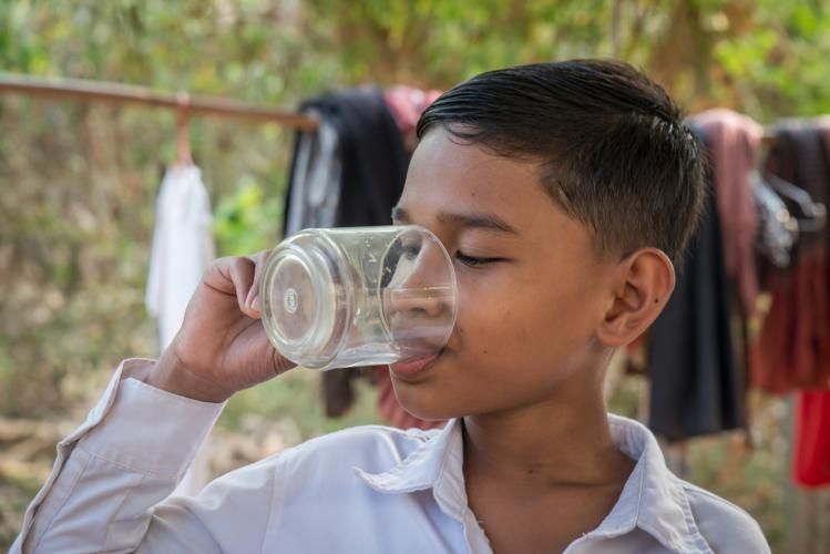 a boy drinking a glass of water