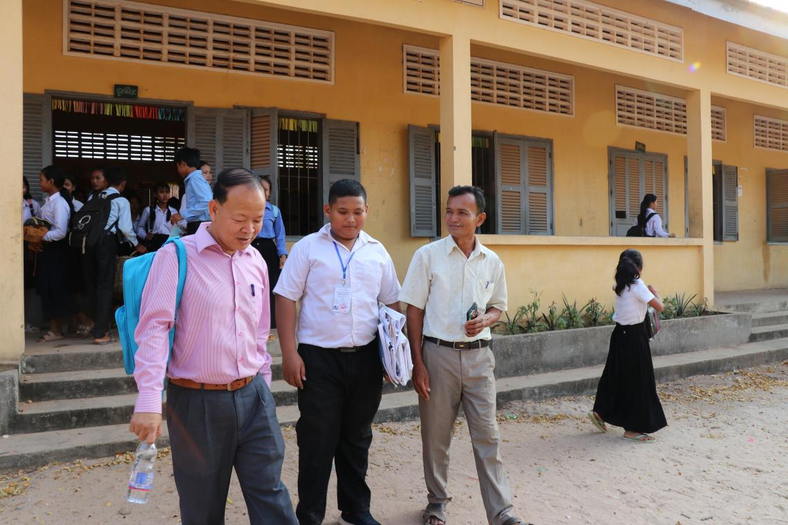School director Phuok Nouk and his student Phanith (16) show UNICEF staff their school.