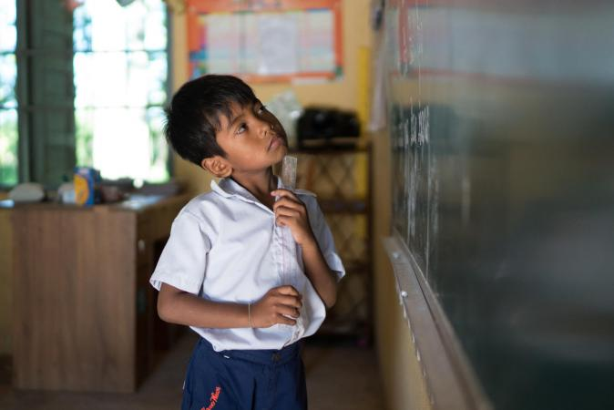 A young boy looks is caught in thought as he looks at what he wrote on the chalkboard at Russey Chroy Primary School in Sa'ang district, Kandal province on July 3, 2018.