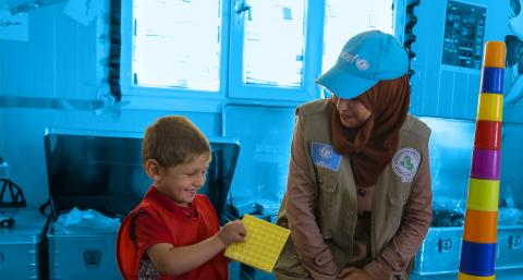 A UNICEF employee sitting with a child
