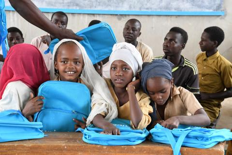 Children in class room receiving school kits
