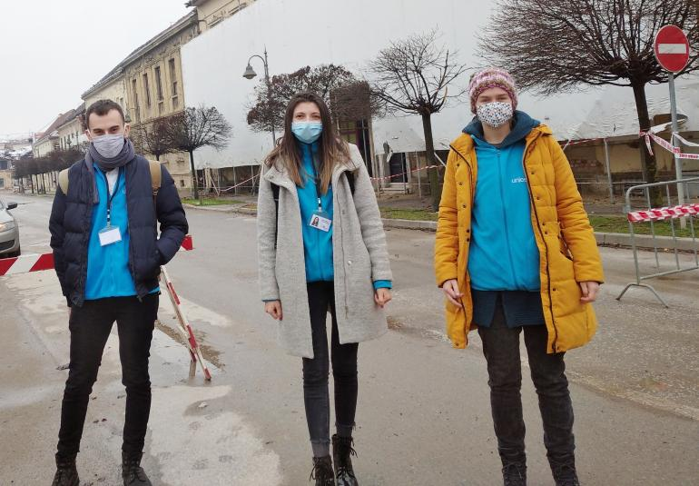 Three psychologists in UNICEF t-shirts standing in the street