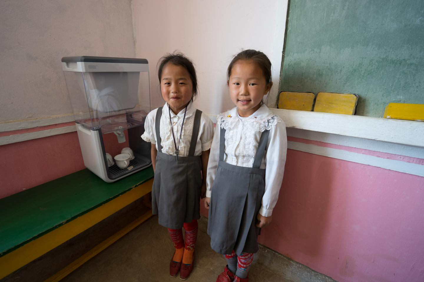 two girls in their classroom besides a unicef-supplied water filter
