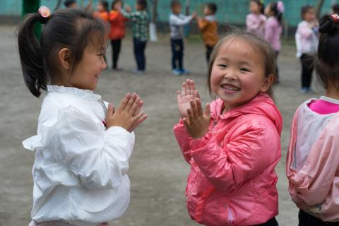 two girls play in a school playground, smiling happily