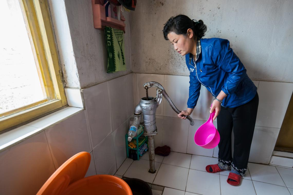 a woman pumping water in her home