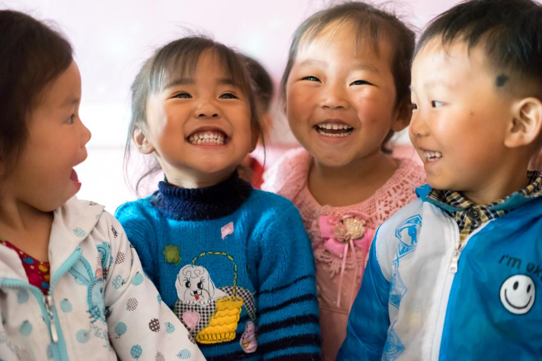 children in a kindergarten smiling and laughing