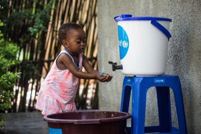 A little girl washes her hands at a UNICEF handwashing station