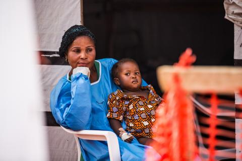 An Ebola survivor cares for a separated young child at the Ebola Treatment Centre in Beni
